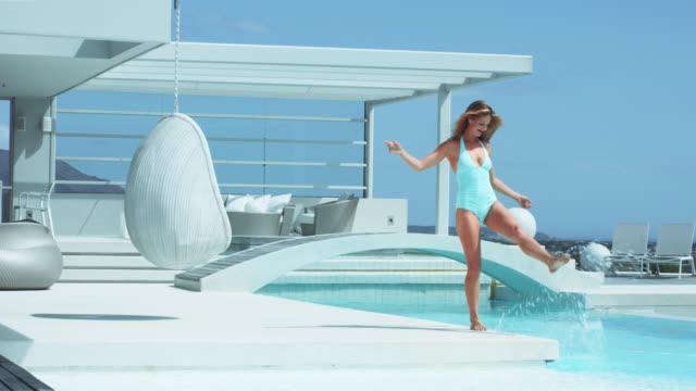 vídeos de stock e filmes b-roll de beautiful blonde woman by pool in luxury villa, kicks water - water's edge