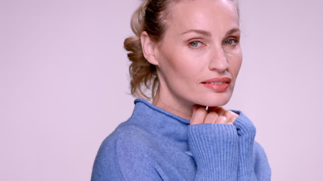 beautiful blonde woman in a blue sweater. - fist stock videos & royalty-free footage