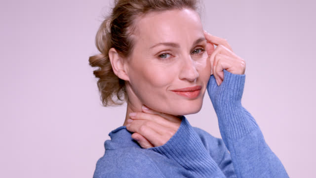 beautiful blonde woman in a blue sweater. - hair back stock videos & royalty-free footage