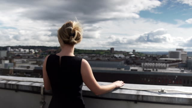 beautiful blonde woman in black dress in wind on rooftop looking out over city with clouds