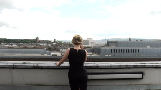 beautiful blonde woman in black dress in wind on rooftop making phone call cell phone mobile city - black dress stock videos & royalty-free footage