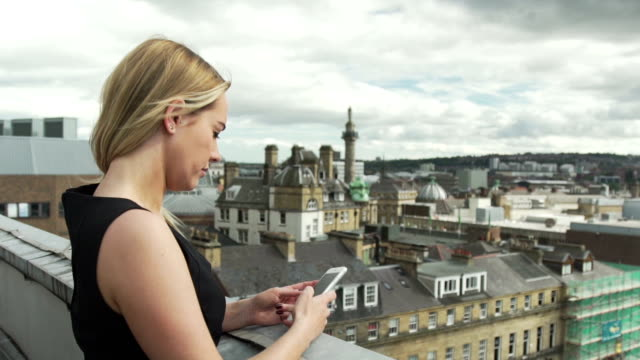 beautiful blonde woman in black dress on rooftop sending text using app iphone cell phone mobile london - black dress stock videos & royalty-free footage