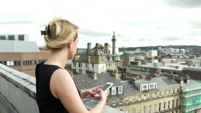 beautiful blonde woman in black dress on rooftop sending text using app on social media and watching pigeons - black dress stock videos & royalty-free footage