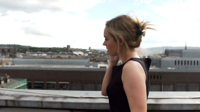 beautiful blonde woman in black dress walking in wind on rooftop making phone mobile cellphone phone call - black dress stock videos & royalty-free footage