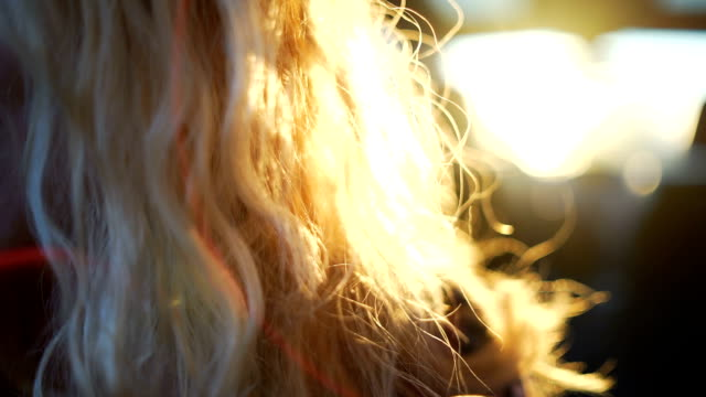 Belle femme blonde dans le coffre de la voiture ouverte au coucher du soleil