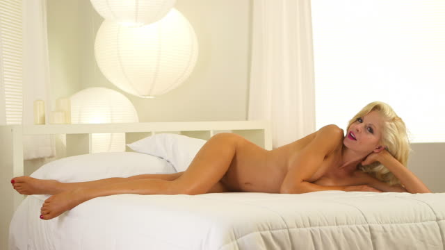 stockvideo's en b-roll-footage met beautiful blonde woman lying in bed - ontbloot bovenlichaam