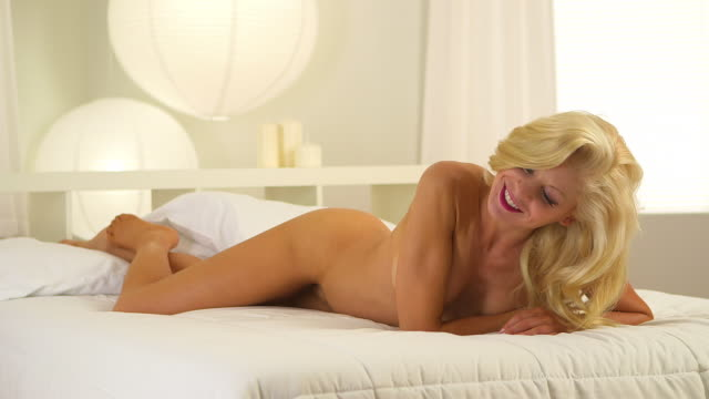 Beautiful blonde woman lying in bed