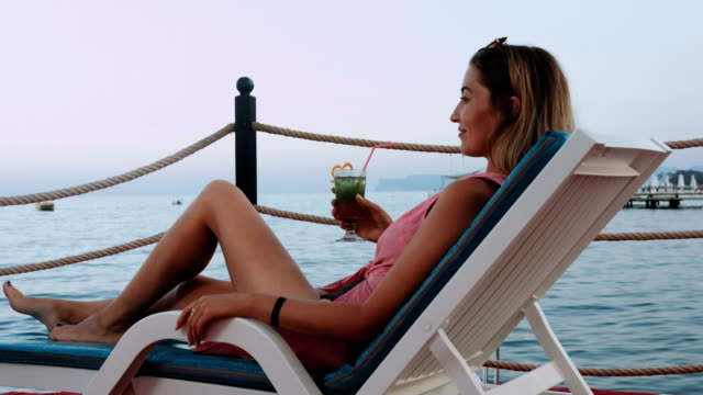 beautiful blonde woman relaxing and drinking cocktail at  coastline - tropical drink stock videos and b-roll footage