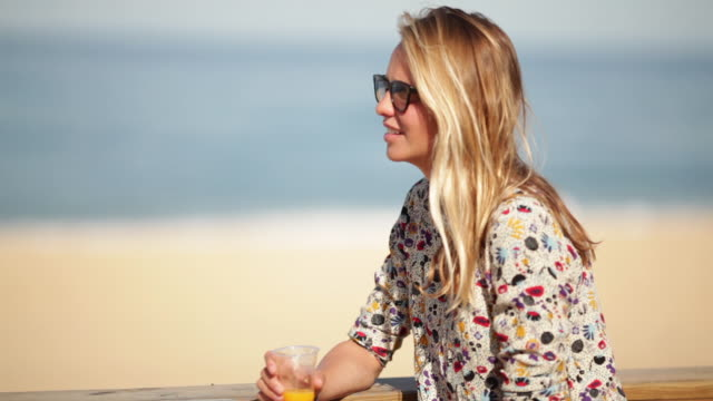 Beautiful blonde woman sitting at beach bar with orange juice listening to a friend talking in the South of France.