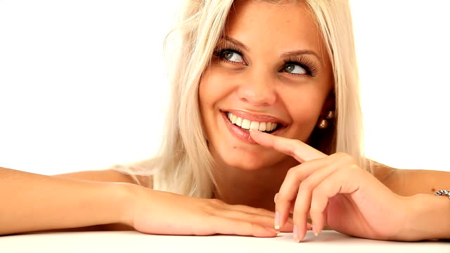 Beautiful blonde woman smiles slyly at camera