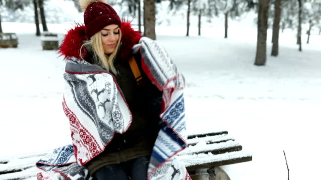 Beautiful blue eyed blonde girl in the snowy woods with warm blanket,