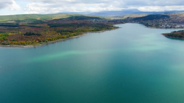 aerial: beautiful blue lake with nearby small town - chiaroscuro stock videos and b-roll footage