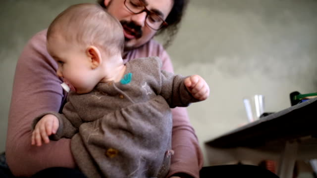 vídeos de stock e filmes b-roll de beautiful blue-eyed baby girl in daddy's lap - genderblend