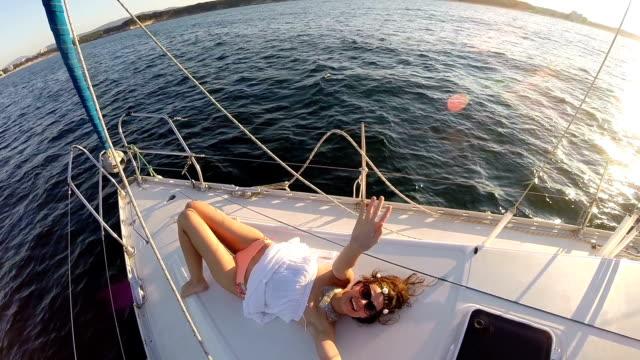 Beautiful boho woman sunbathing on an yacht
