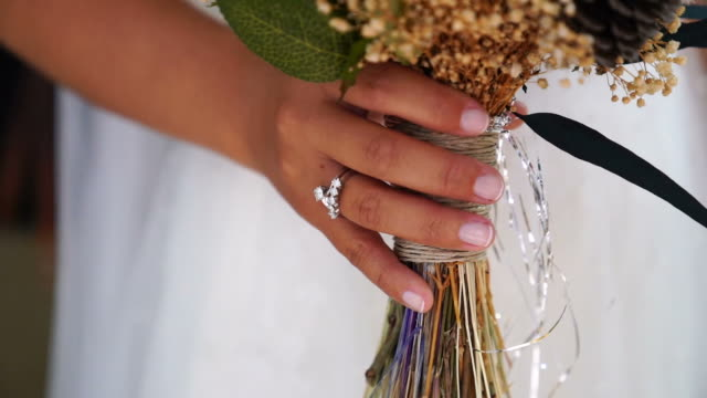 beautiful bridal bouquet in hands of young bride dressed in white wedding dress. - bunch of flowers stock videos and b-roll footage