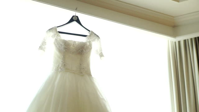 beautiful bridal dress hanging in the room. - wedding dress stock videos and b-roll footage