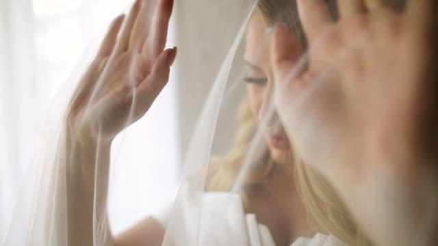 vídeos y material grabado en eventos de stock de hermosa novia jugando con el velo de la boda mientras está de pie cerca de la ventana - back lit