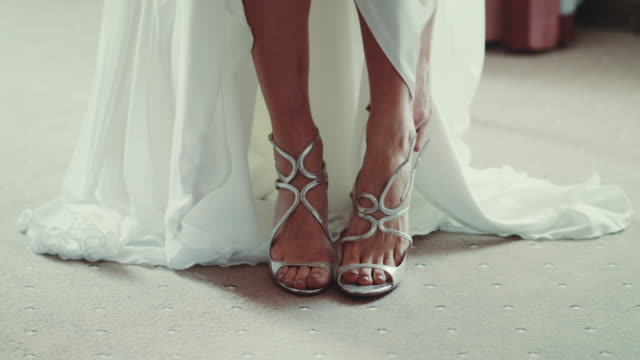 Beautiful Bride Putting On Shoes For Wedding Day
