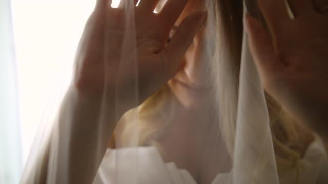 vídeos y material grabado en eventos de stock de hermosa novia usando el velo antes de la ceremonia de la boda - back lit
