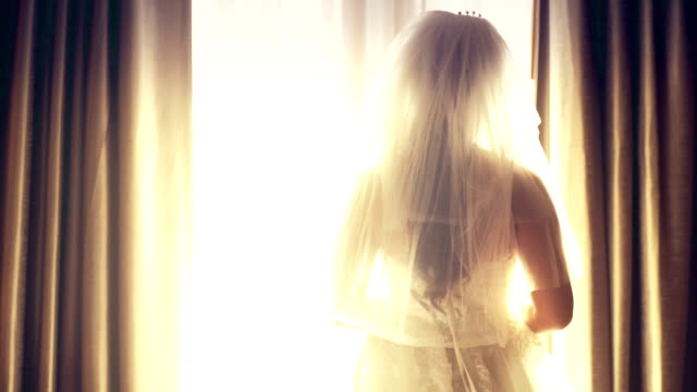 Beautiful bride with a veil looking through the window in the hotel.
