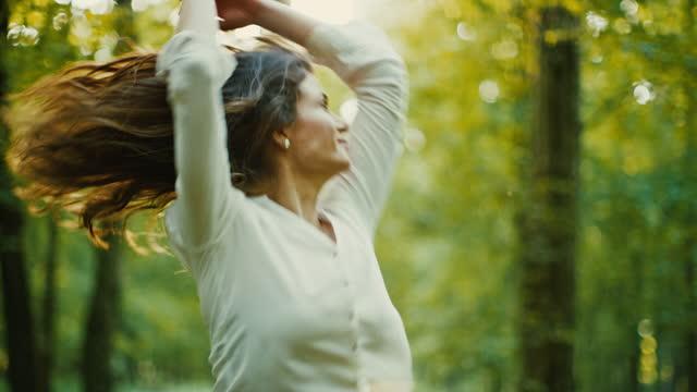stockvideo's en b-roll-footage met slo mo mooie brunette houdt van de natuur, ze stuitert en draait in een zonnig groen bos - sunny