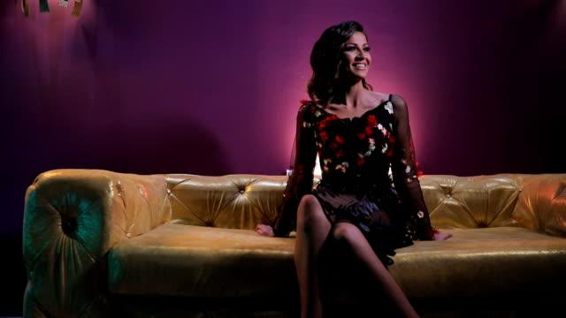 vídeos de stock, filmes e b-roll de bela morena sentada no sofá colorido ouro - de pernas cruzadas