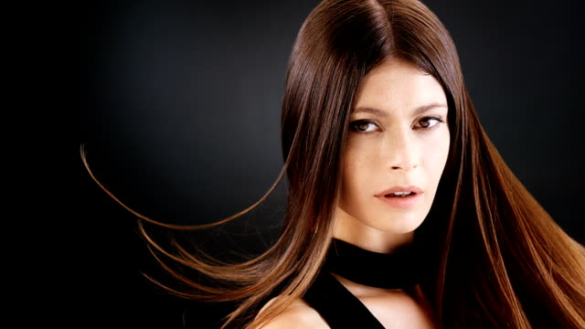 beautiful brunette tossing her long hair. montage - shampoo per capelli video stock e b–roll