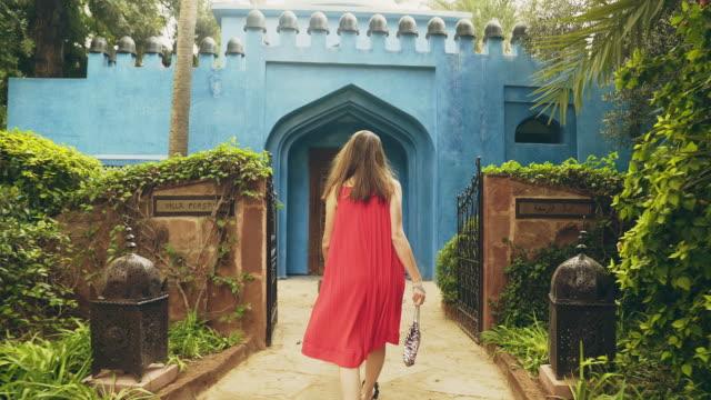 vídeos de stock e filmes b-roll de beautiful brunette visiting tropical garden. moroccan architecture - eastern european culture