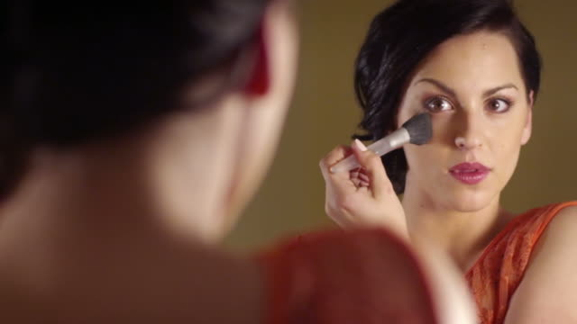 Beautiful brunette woman applying make-up