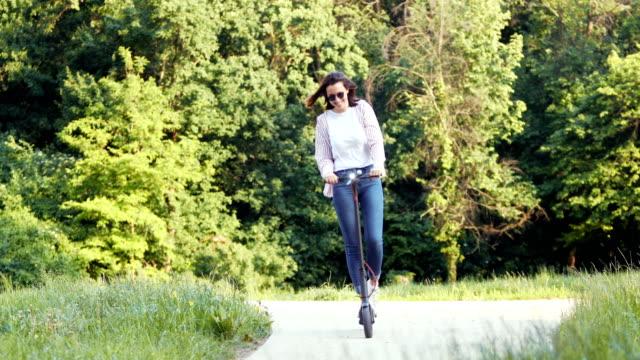 vídeos y material grabado en eventos de stock de hermosa mujer morena b rodando en el scooter de kick en el parque público - equilibrio vida trabajo