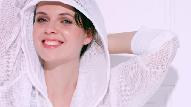 vidéos et rushes de beautiful brunette woman in white hooded top - d'ascendance européenne