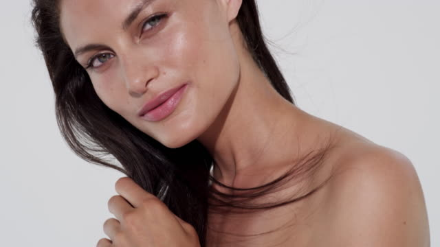 stockvideo's en b-roll-footage met beautiful brunette woman looks at camera and brushes then touches her long brunette hair - haar borstelen