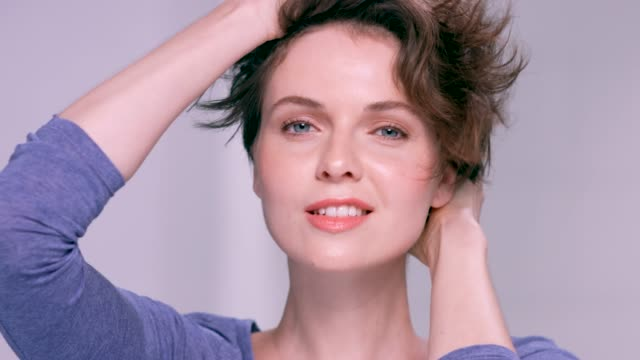 Beautiful brunette woman plays with her short hair in slow motion.