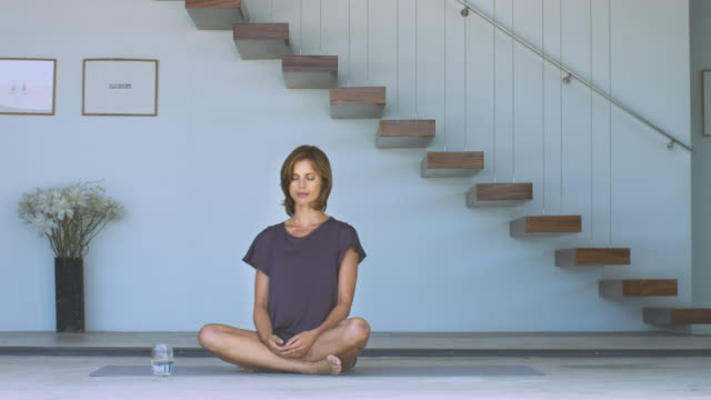 beautiful brunette woman sitting cross-legged on a yoga mat. - cross legged stock videos & royalty-free footage