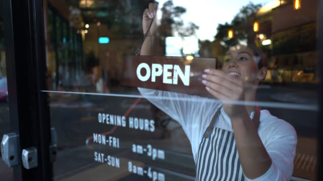 beautiful business owner of a bakery putting up the open sign at the entrance looking very happy - owner stock videos & royalty-free footage