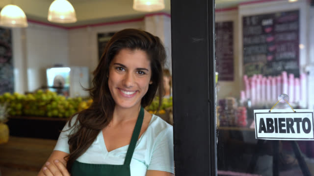 vídeos de stock e filmes b-roll de beautiful business owner of a juice bar walking up to the entrance to put an open sign on the window and looking to the camera smiling - negócios
