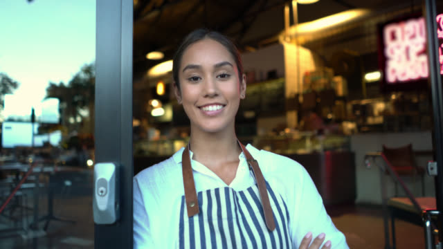 beautiful business owner of her bakery standing leaning on the entrance with arms crossed smiling - autorità video stock e b–roll