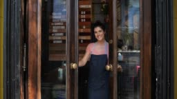 Beautiful business owner opening the doors and welcoming to her restaurant with her hands while looking at camera