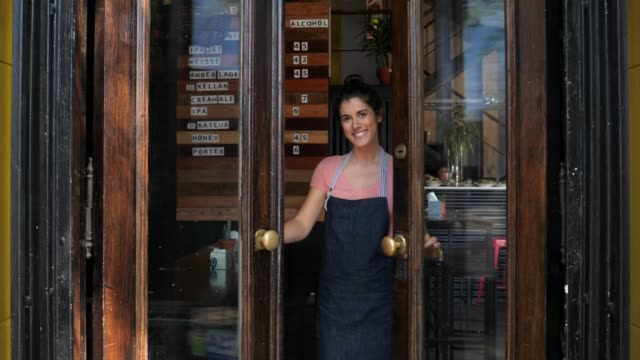 vídeos de stock e filmes b-roll de beautiful business owner opening the doors and welcoming to her restaurant with her hands while looking at camera - acenar