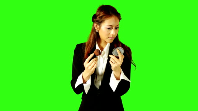 beautiful business woman applying make up with green screen background - keyable stock videos & royalty-free footage