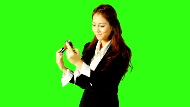 stockvideo's en b-roll-footage met beautiful business woman applying make up with green screen background - keyable