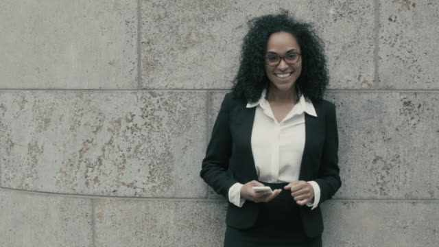 stockvideo's en b-roll-footage met beautiful business woman laughing at camera, holding smart phone - blazer