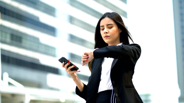 beautiful business woman playing smart phone and checking time by looking on wrist watch at modern office background - suit stock videos & royalty-free footage