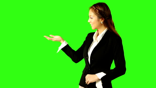 stockvideo's en b-roll-footage met beautiful business woman presenting with green screen background - keyable
