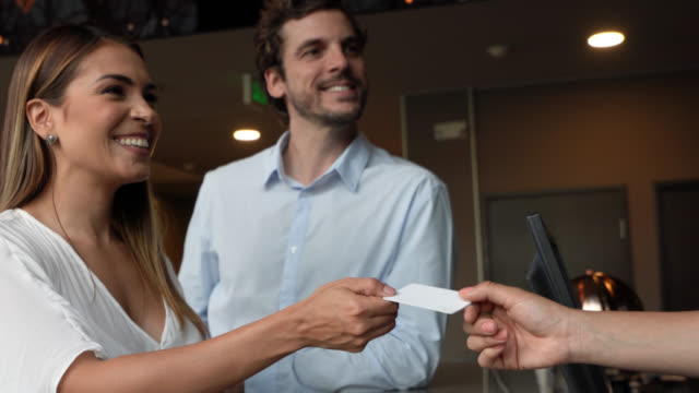 beautiful business woman receiving key for their hotel room and partner embracing her - receptionist video stock e b–roll
