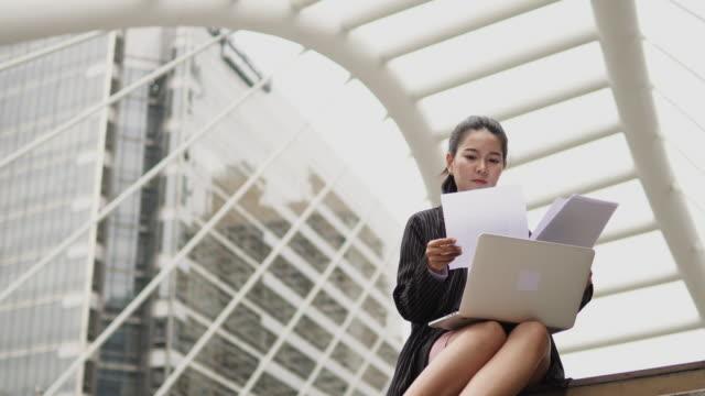 schöne geschäftsfrau sitzen und arbeiten auf einem laptops in ihren händen im freien. - politiker stock-videos und b-roll-filmmaterial