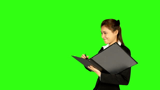 stockvideo's en b-roll-footage met beautiful business woman taking a note with green screen background - keyable