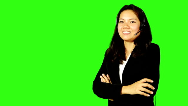 beautiful business woman wearing headphone with green screen background - keyable stock videos and b-roll footage