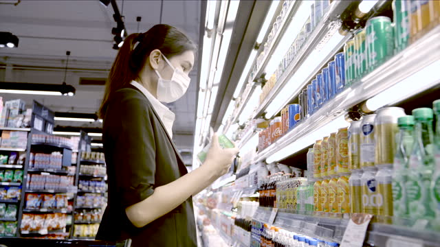 beautiful business women wearing protective face masks shopping in a supermarket at the market mall. - frozen food stock videos & royalty-free footage