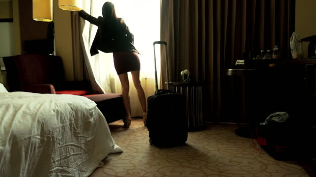 Beautiful businesswoman arriving in a hotel bedroom.